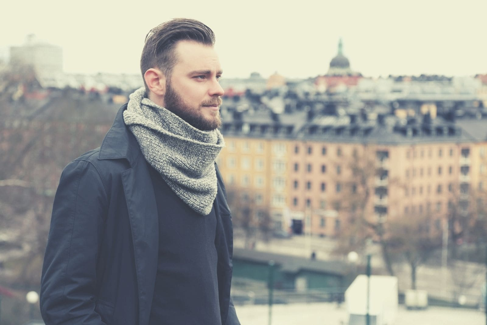 lonely pensive man with a grey scarf standing with the city behind
