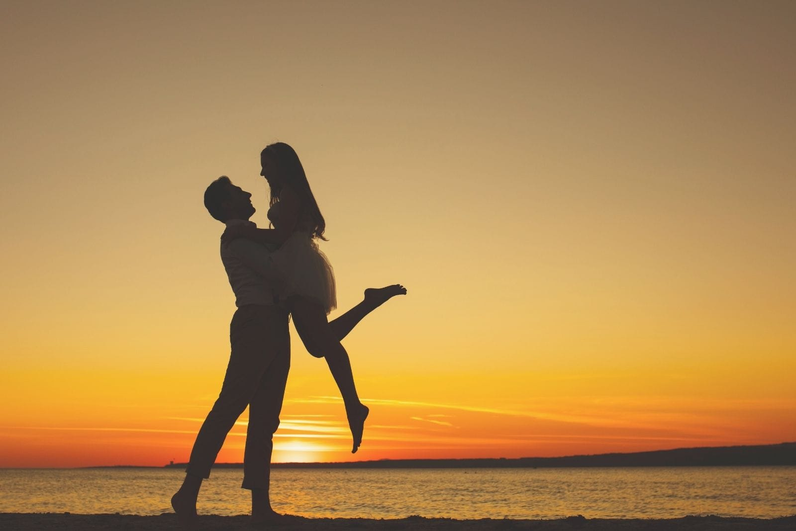 lovely couple in love silhouette during sunrise near a body of water