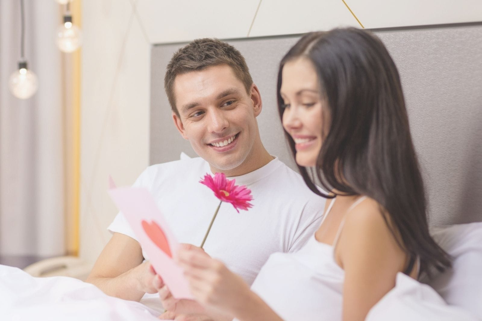 loving couple in bed reading love letter with a flower