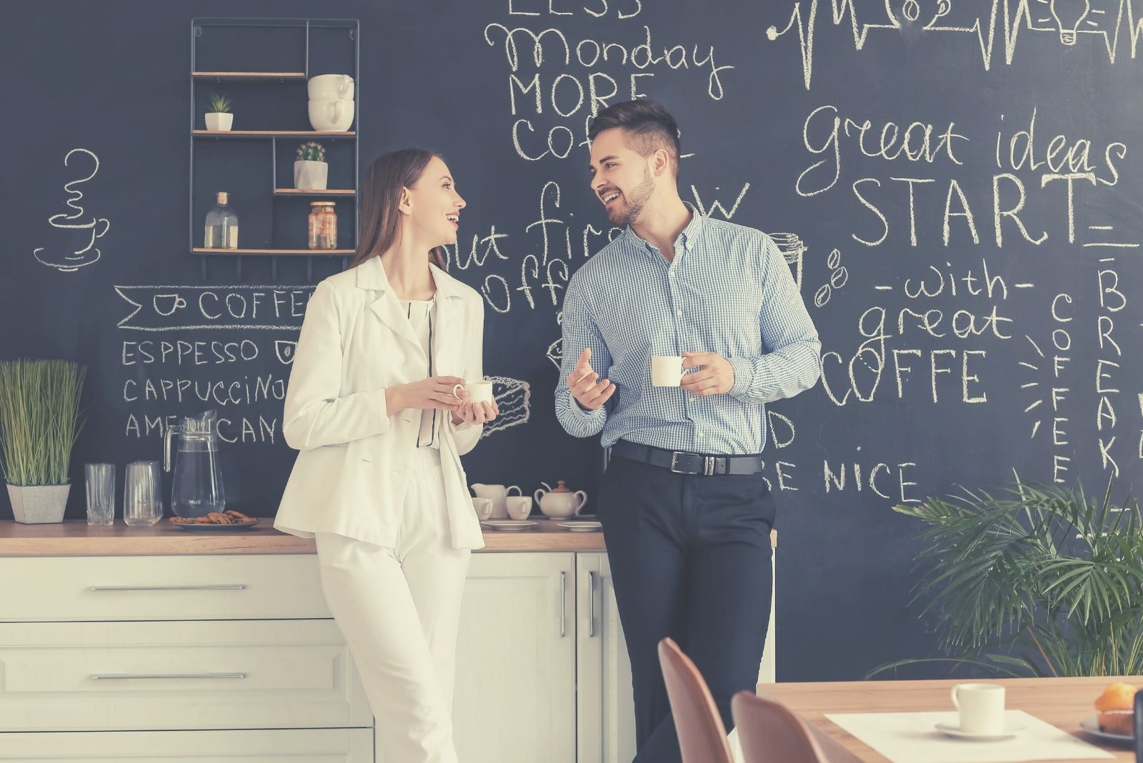 male and female workers drinking coffee in the pantry during their break