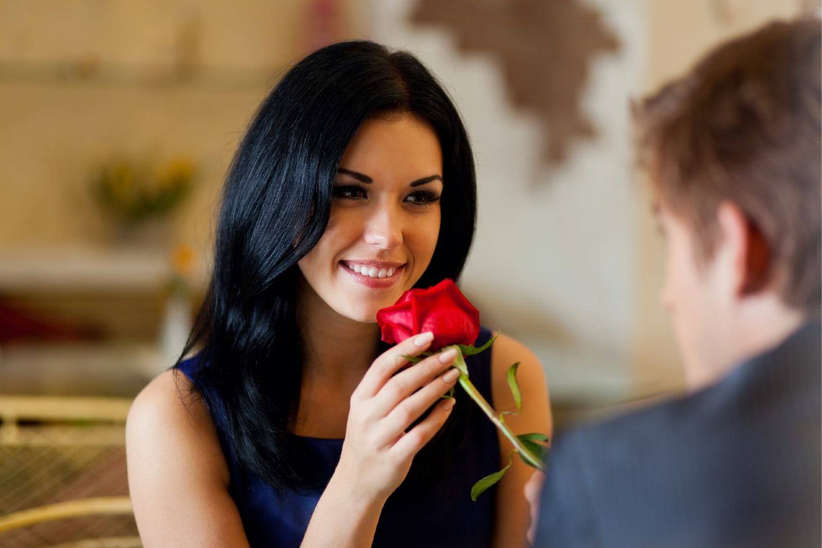 man giving red rose to woman while sitting at table