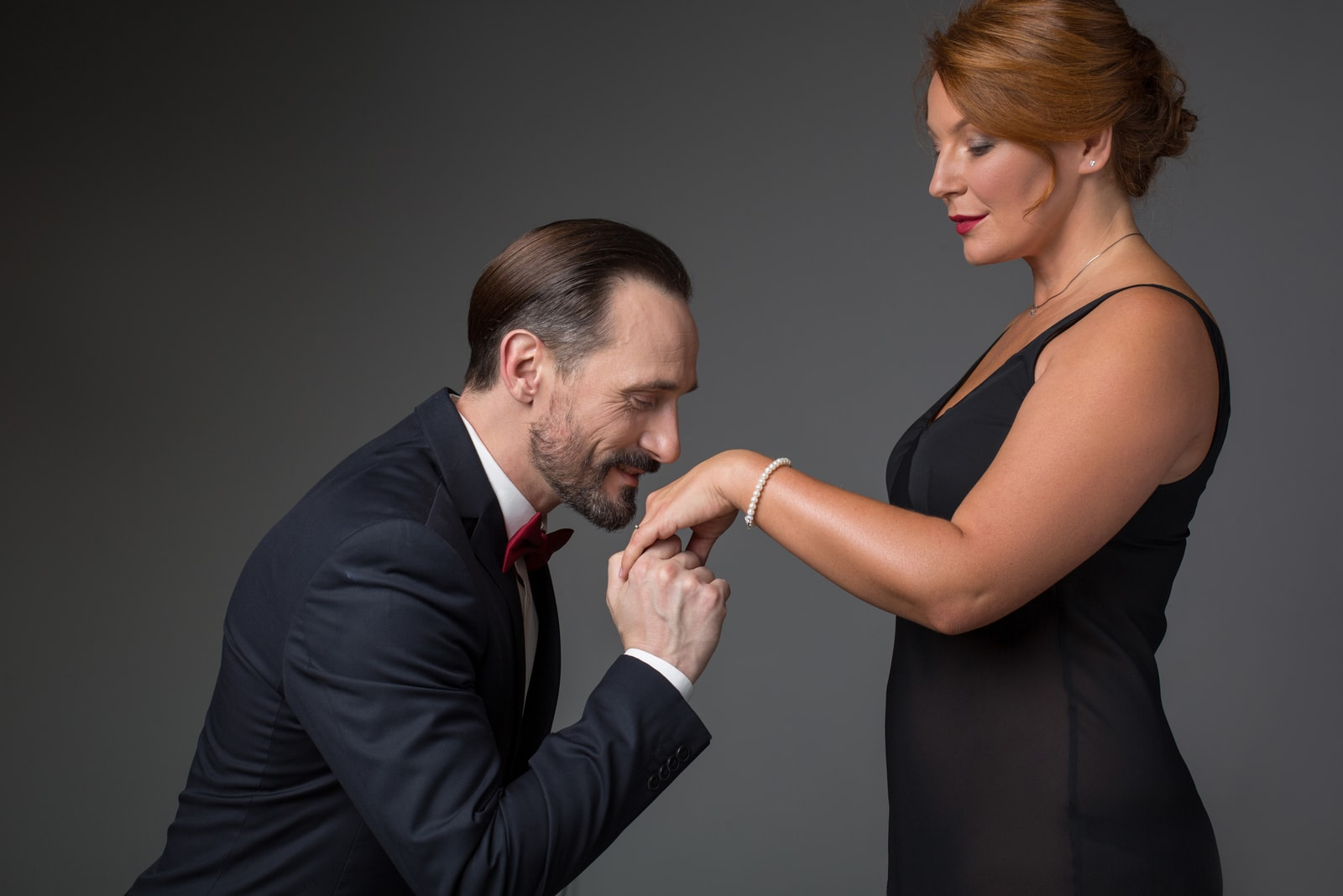 man holding female hand with gold ring and kissing it.