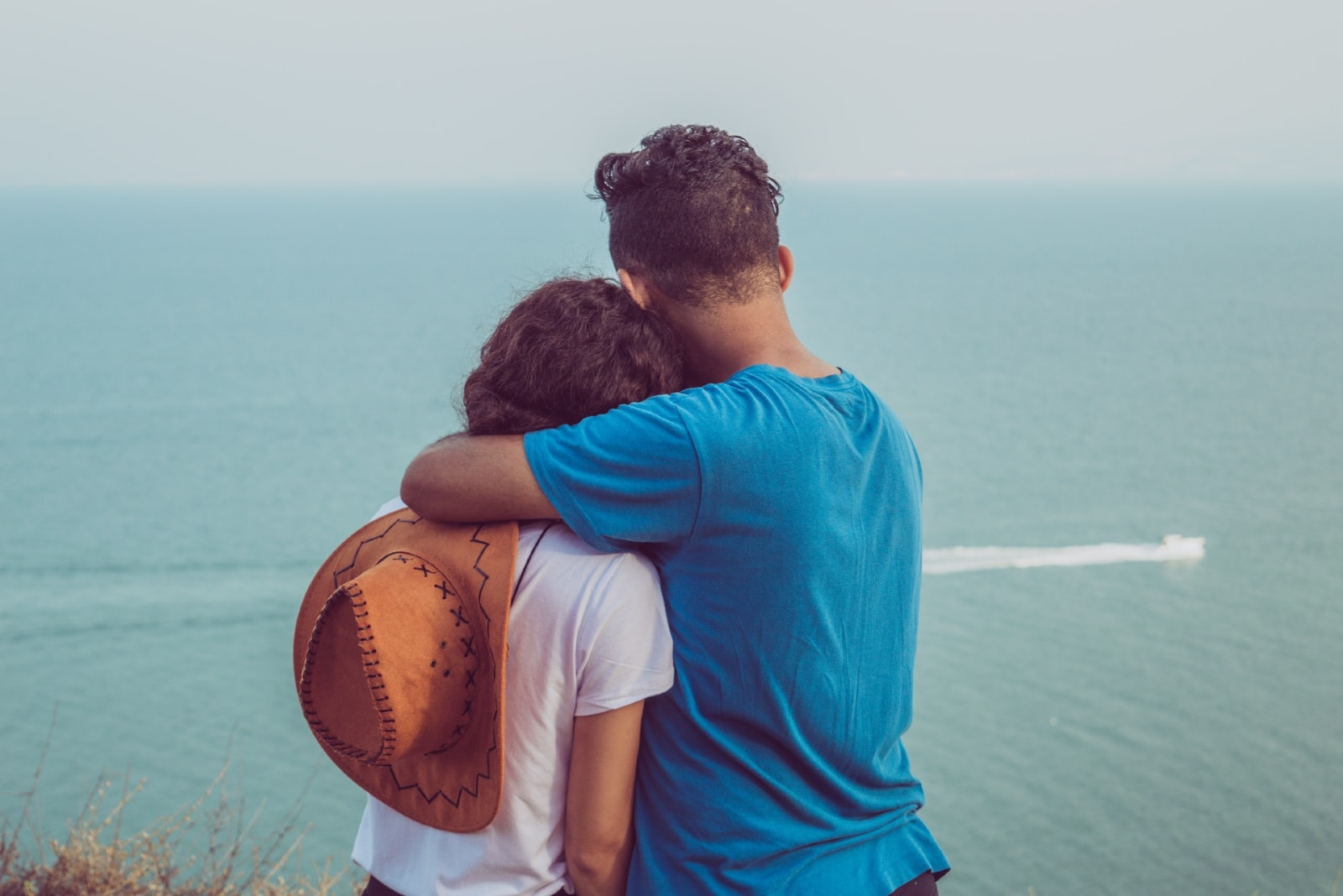 man in blue t-shirt hugging woman while looking at sea
