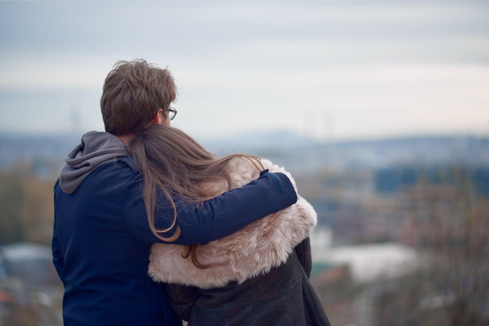man in black jacket hugging woman outdoor