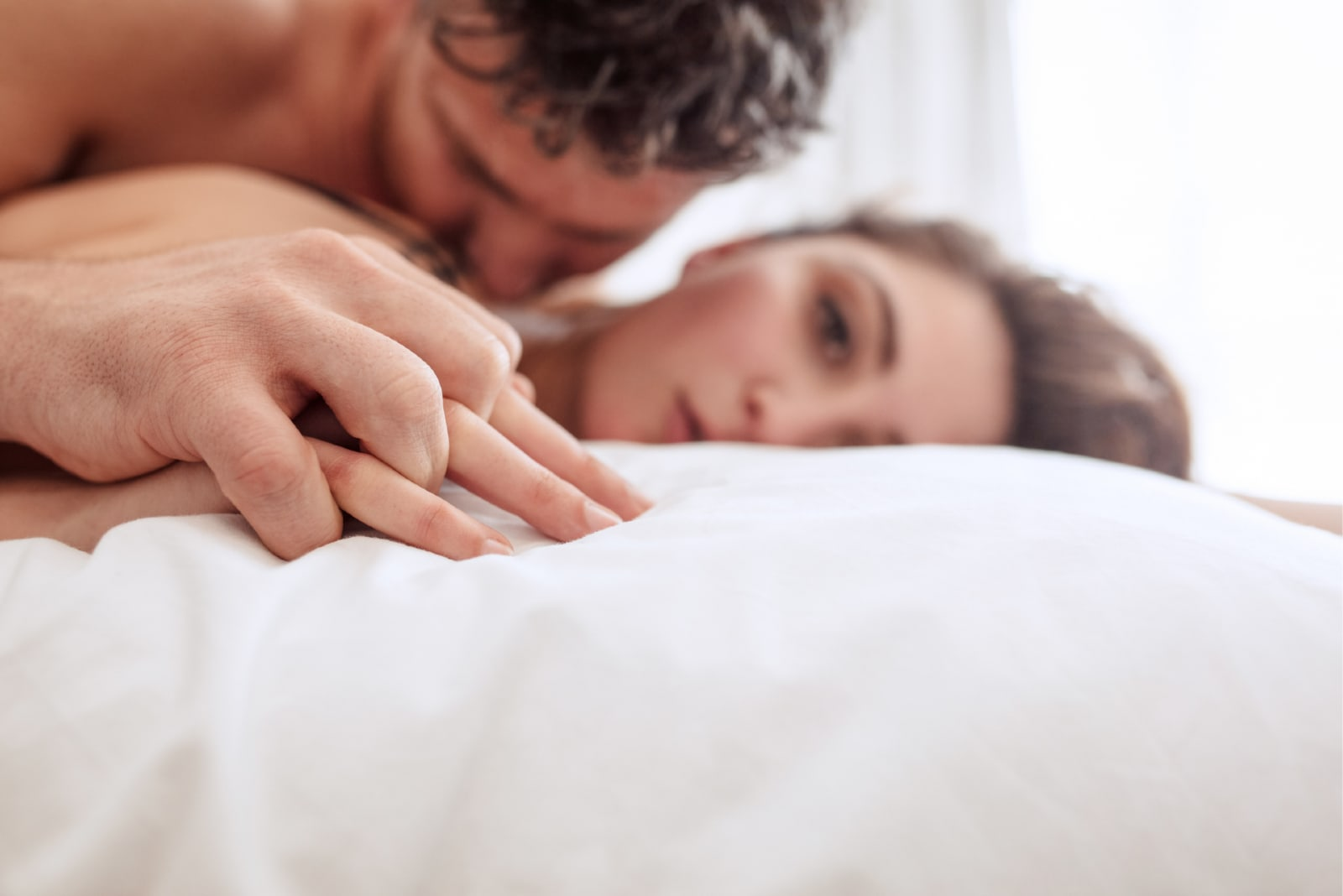 man kissing woman while laying on bed