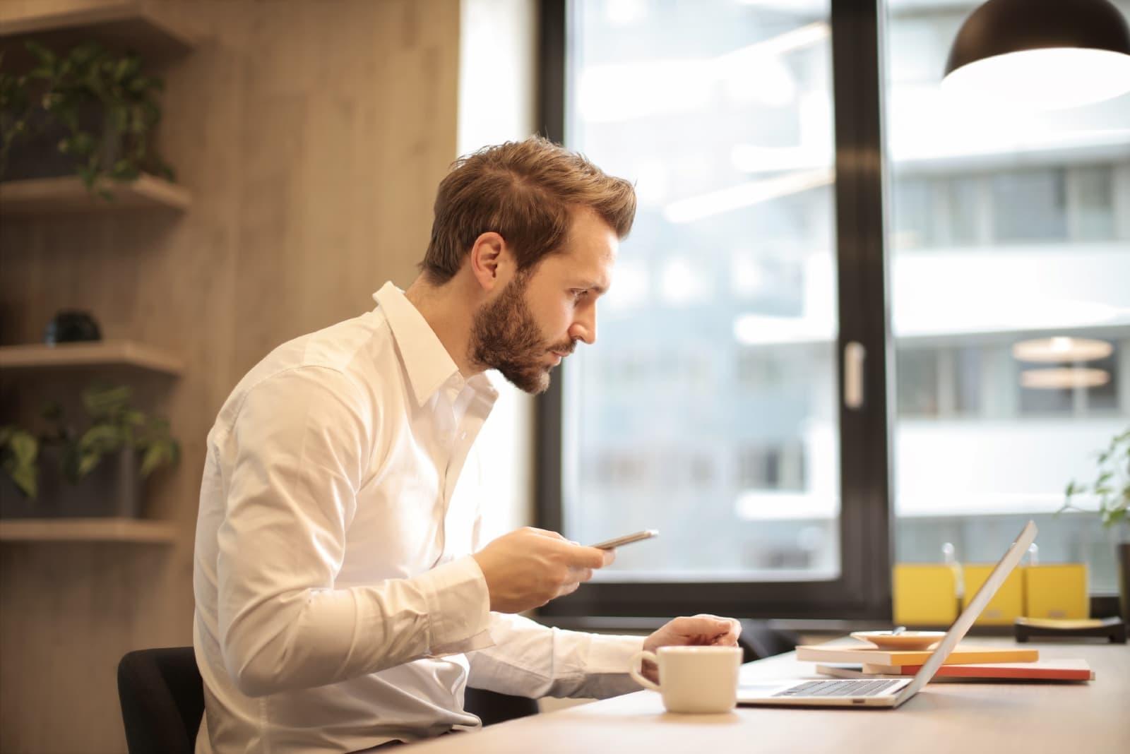 man in white shirt looking at laptop