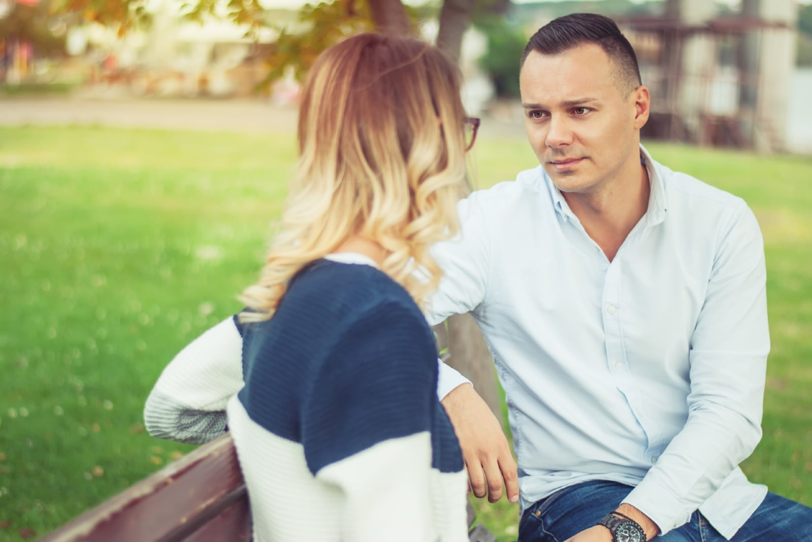 man looking at woman while sitting on bench