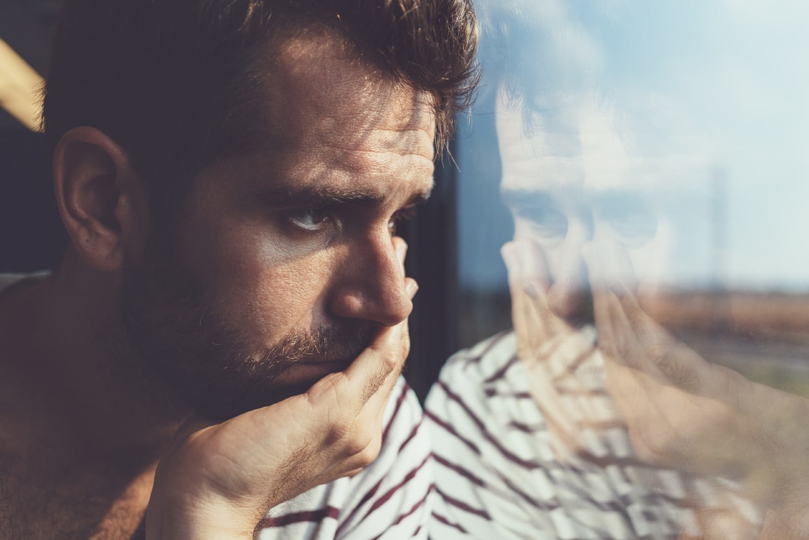 pensive man in striped shirt looking through window