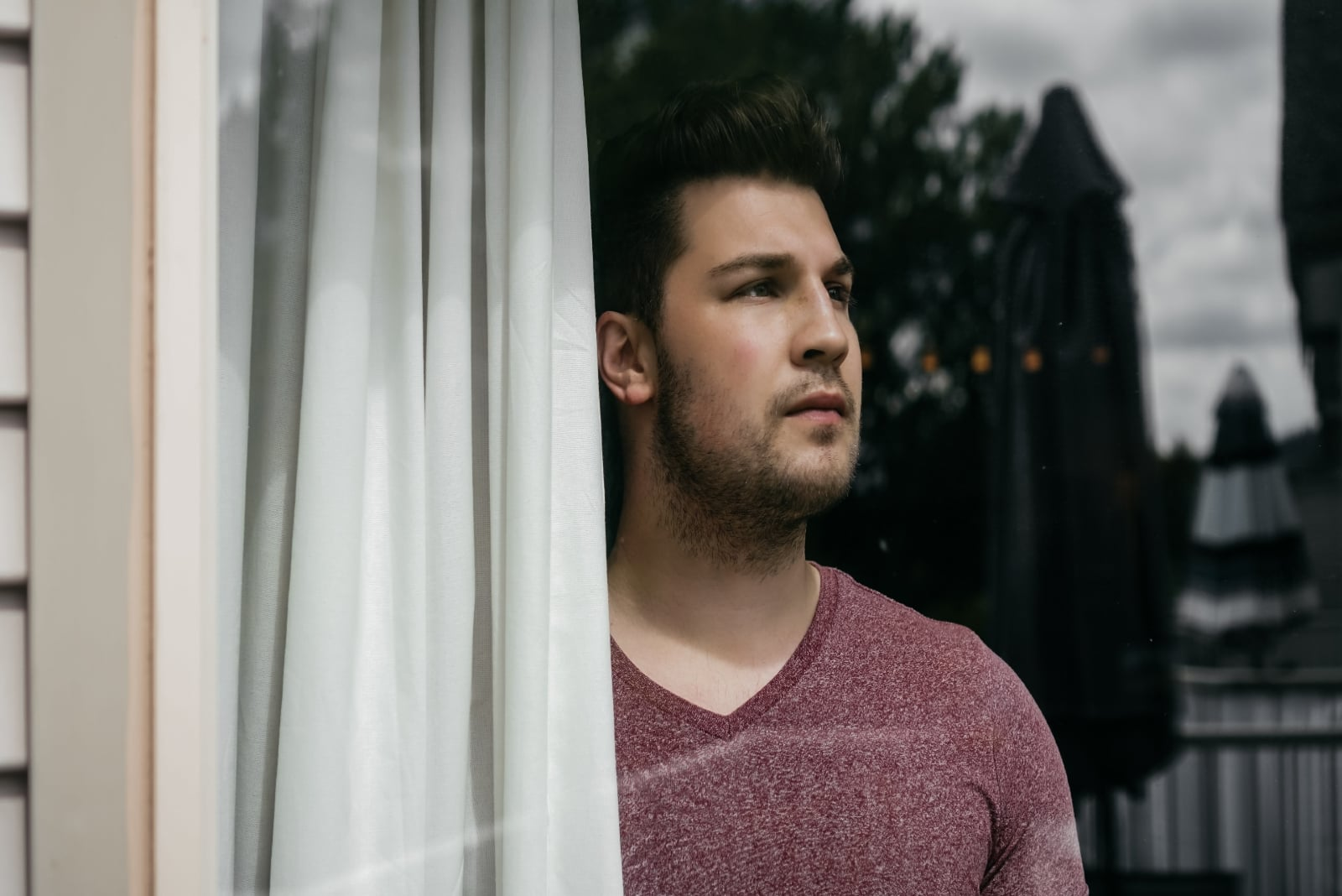man looking through window while standing near white curtain