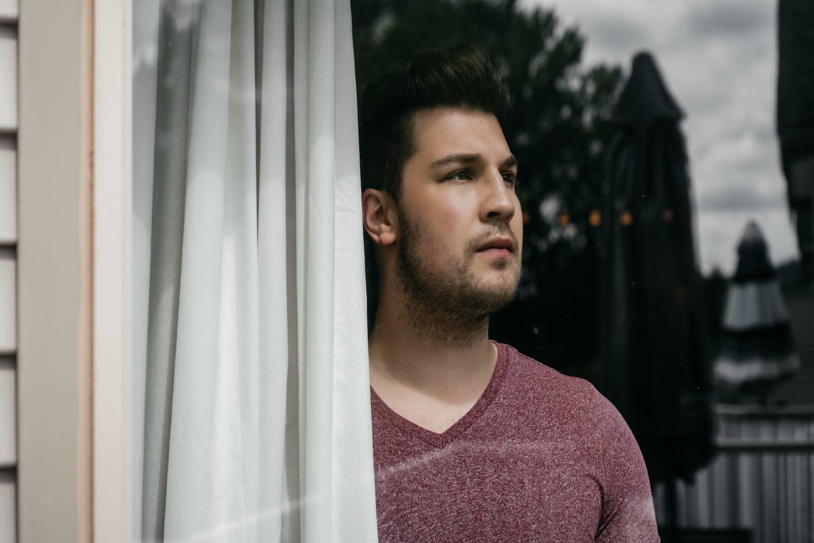 man looking through window while standing near white curtain