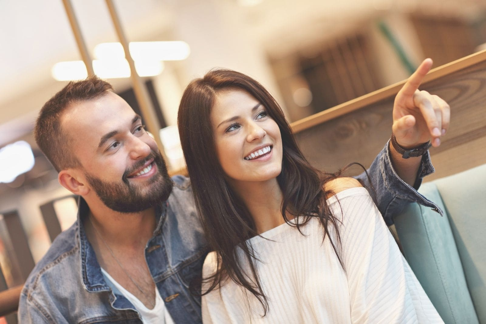 man pointing to something while dating with his girlfriend in and indoor cafe