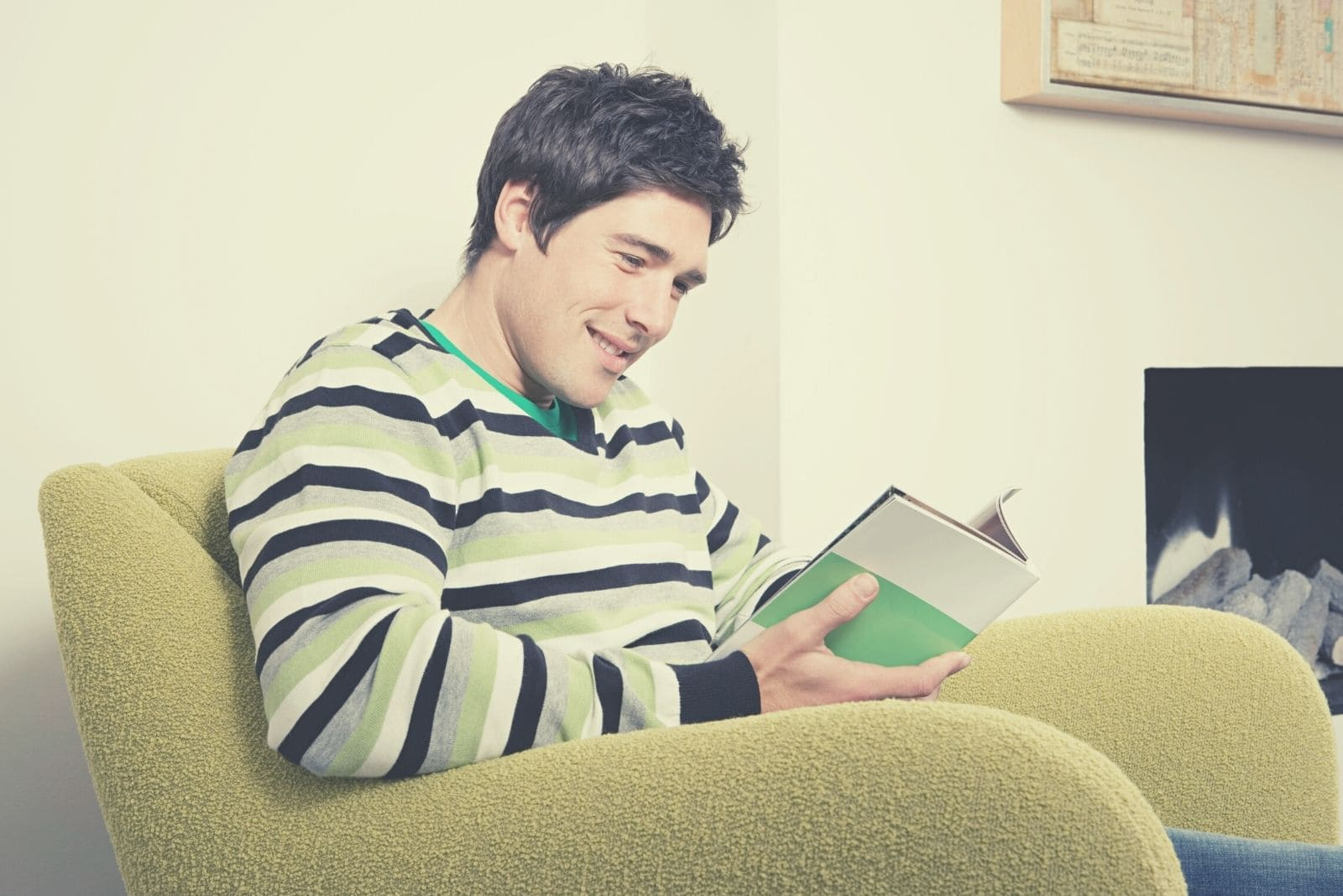 man reading book alone while sitting in the nook