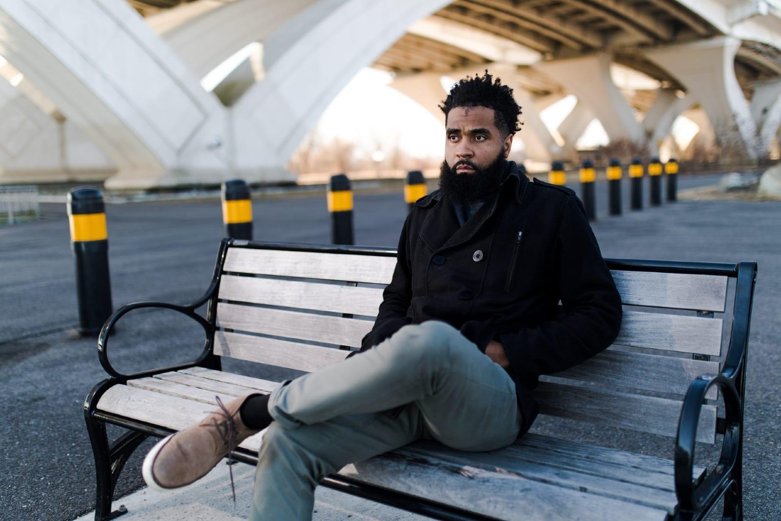 pensive man in black jacket sitting on bench