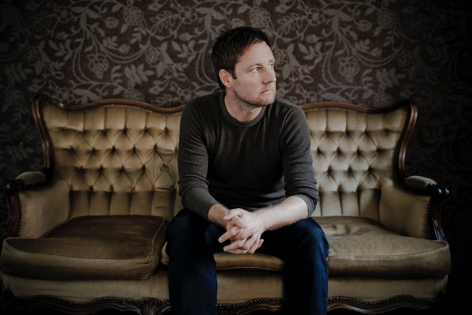 pensive man in gray shirt sitting on couch