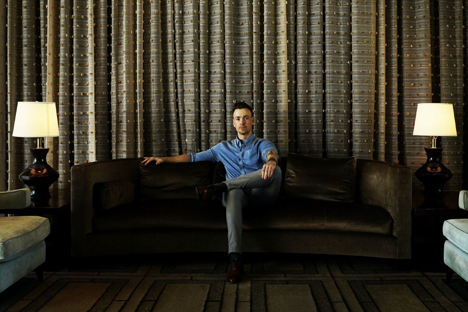 pensive man in denim shirt sitting on couch