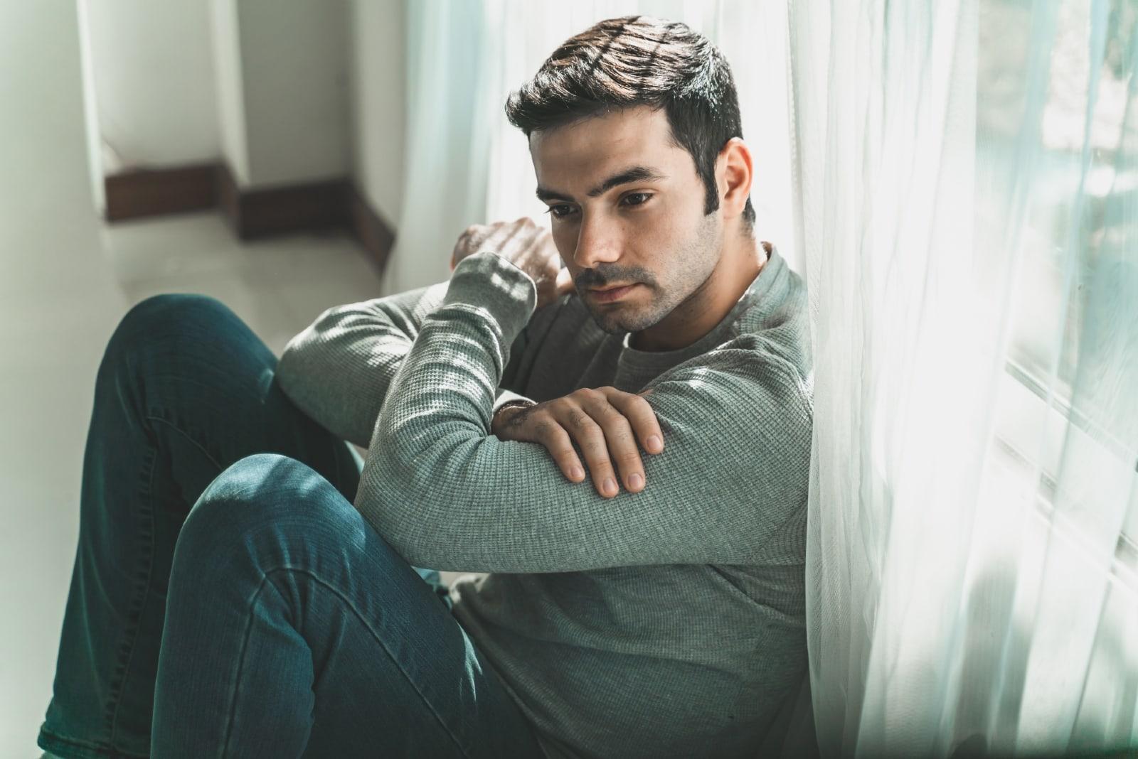 sad man in gray top sitting on floor thinking