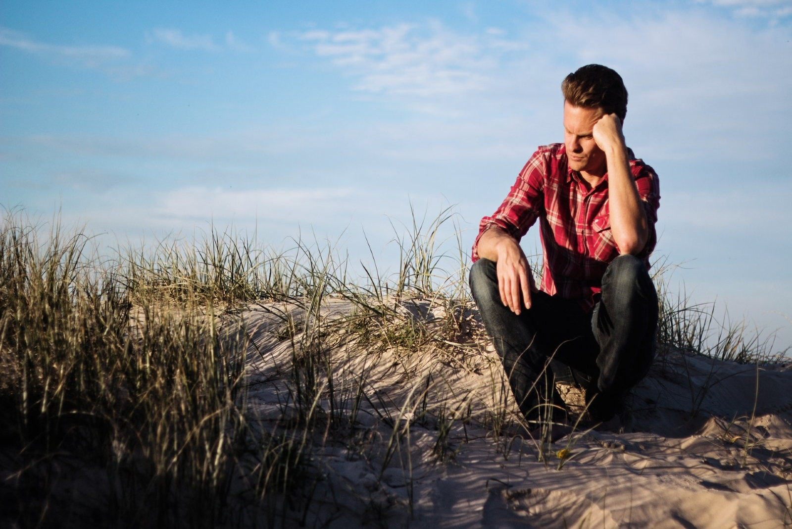 pensive man in red shirt sitting on sand
