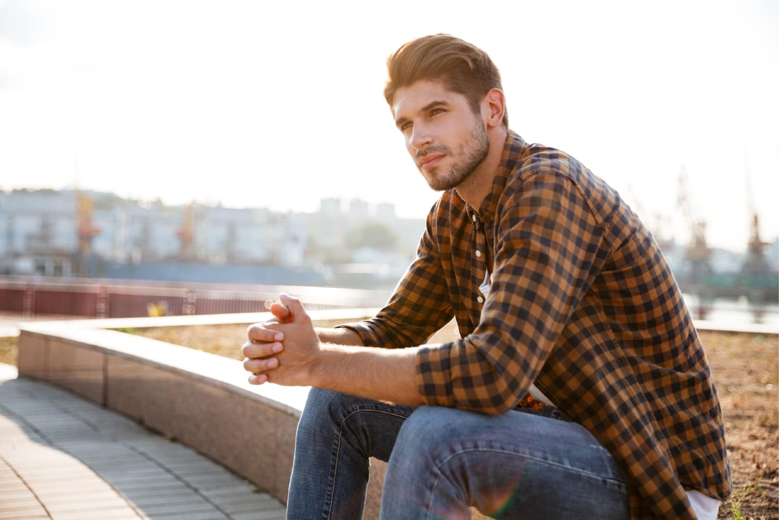 pensive man in plaid shirt sitting outdoor