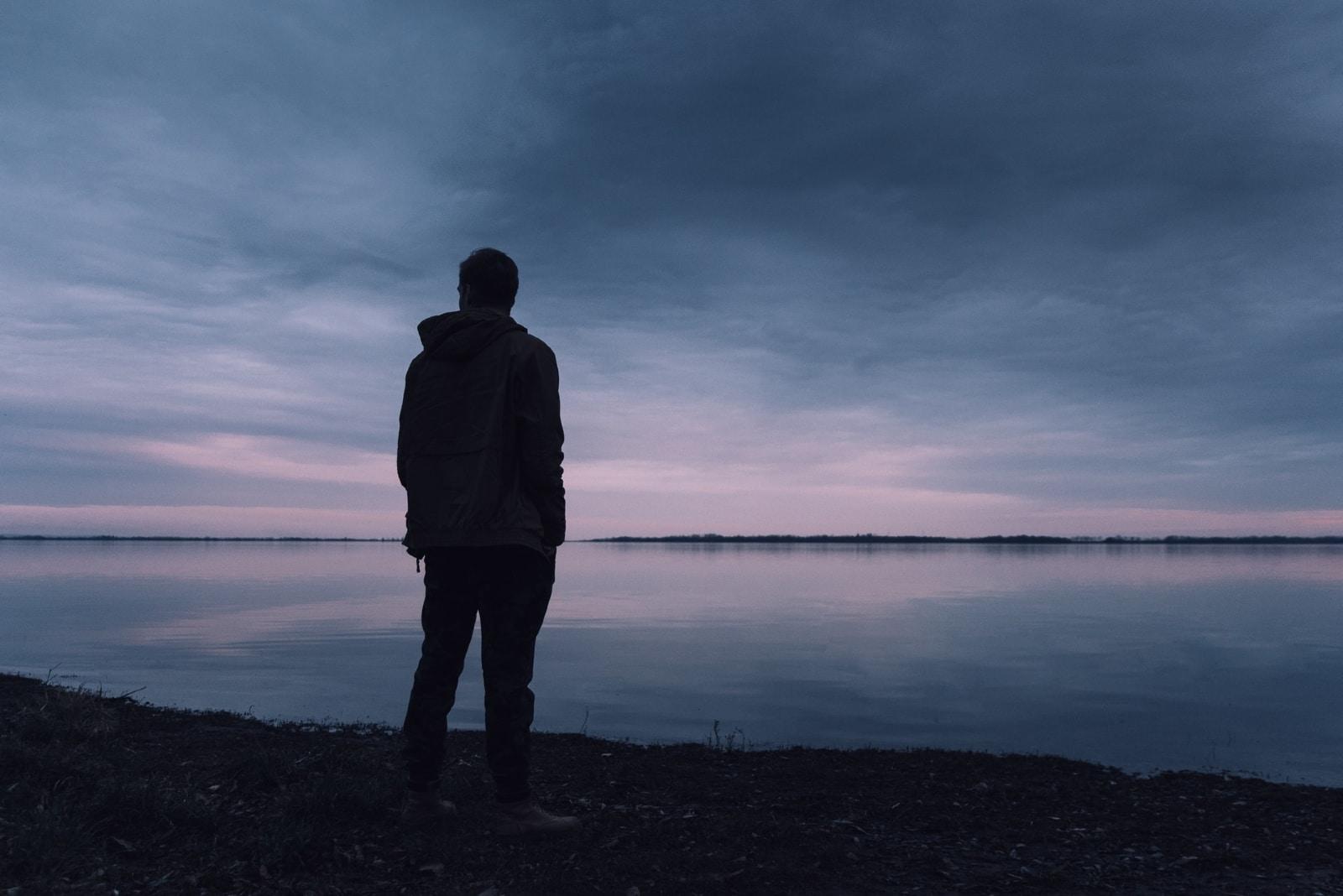man in gray jacket standing near water