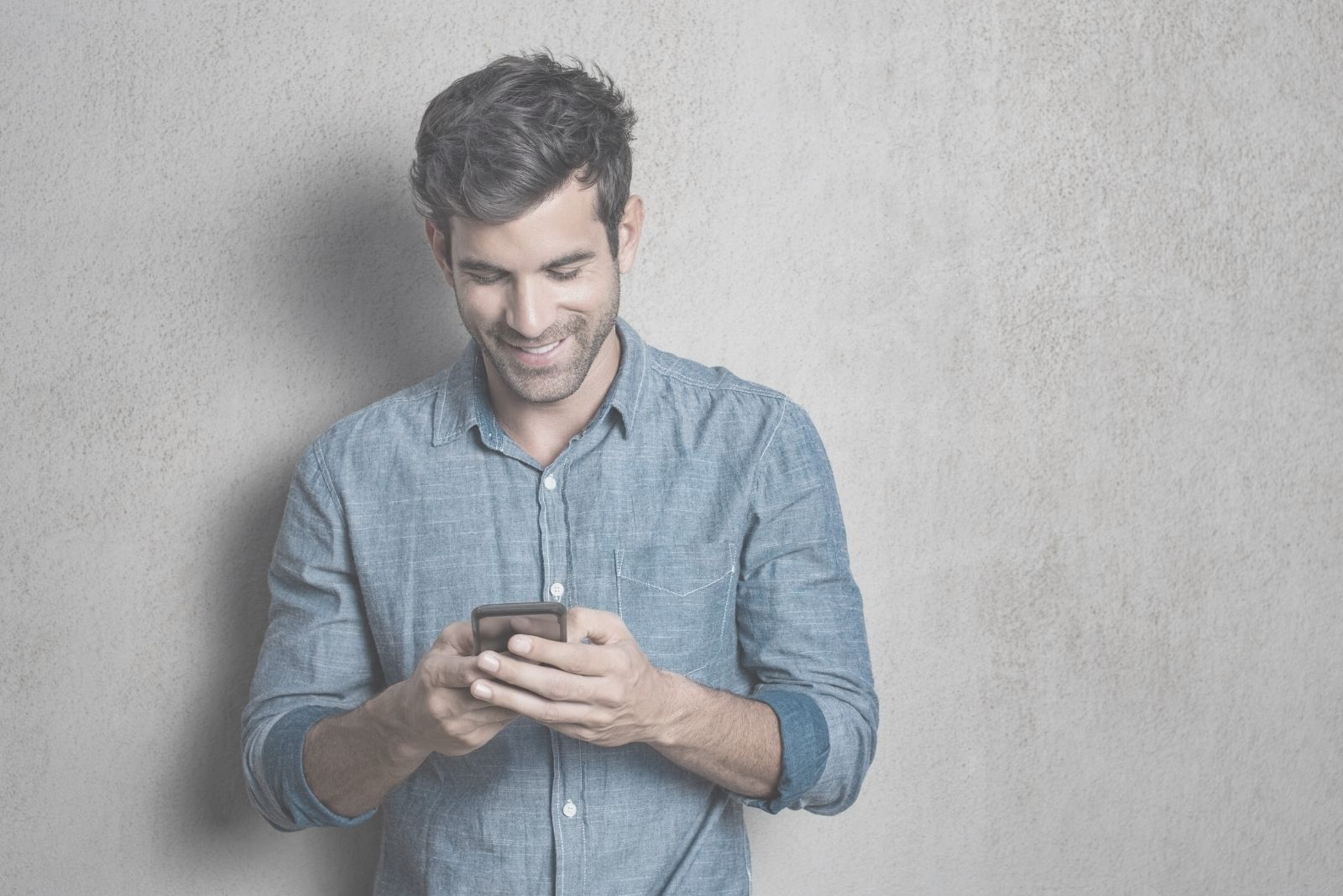 man texting and smiling and standing leaning on the white wall