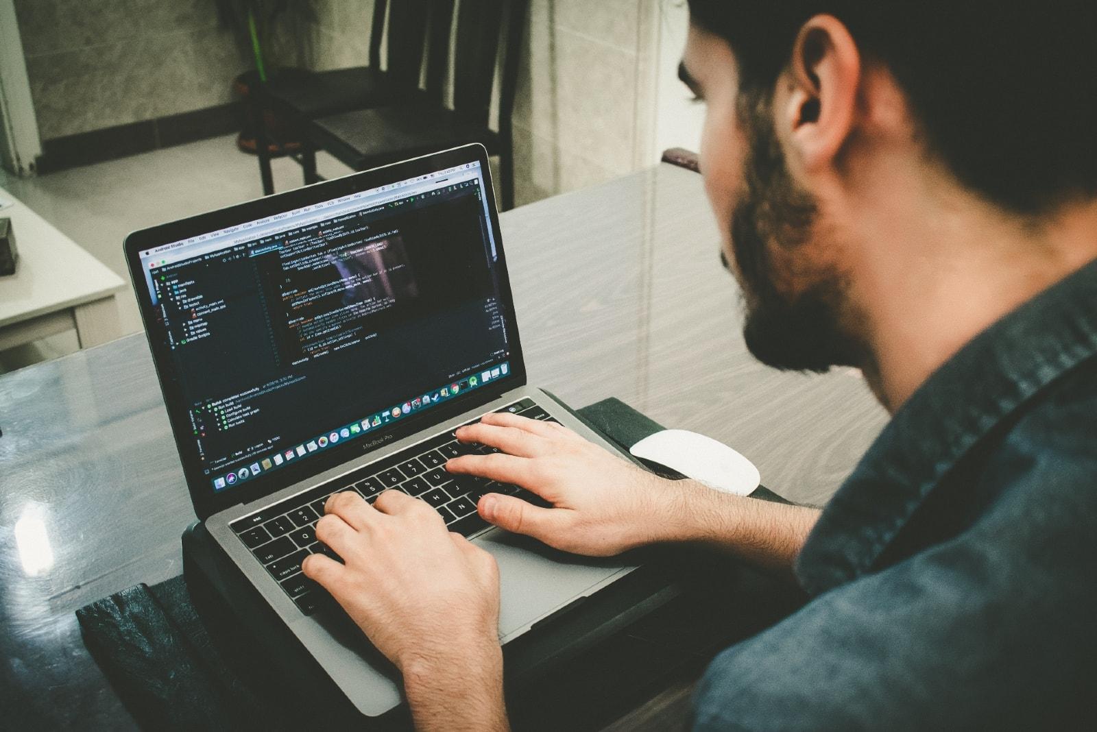 man using laptop while sitting at table