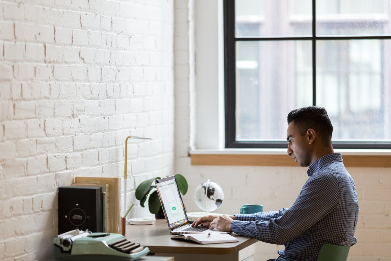 man using laptop while sitting in office
