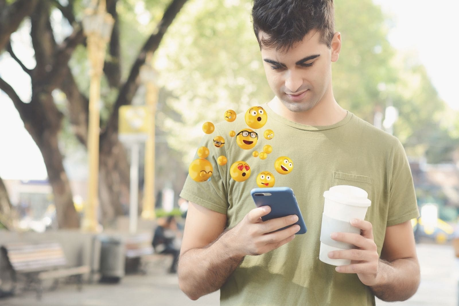 man using smartphone sending emojis and holding cup of coffee while walking in the park