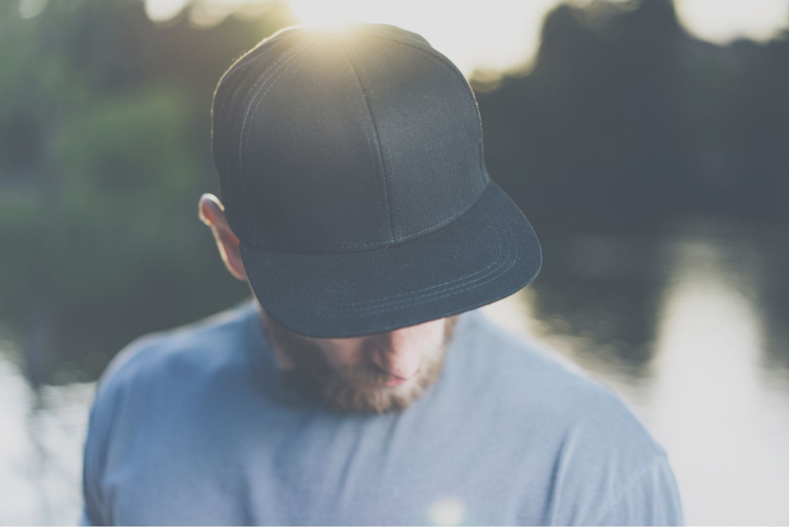man with a cap bowing down sad standing outdoors