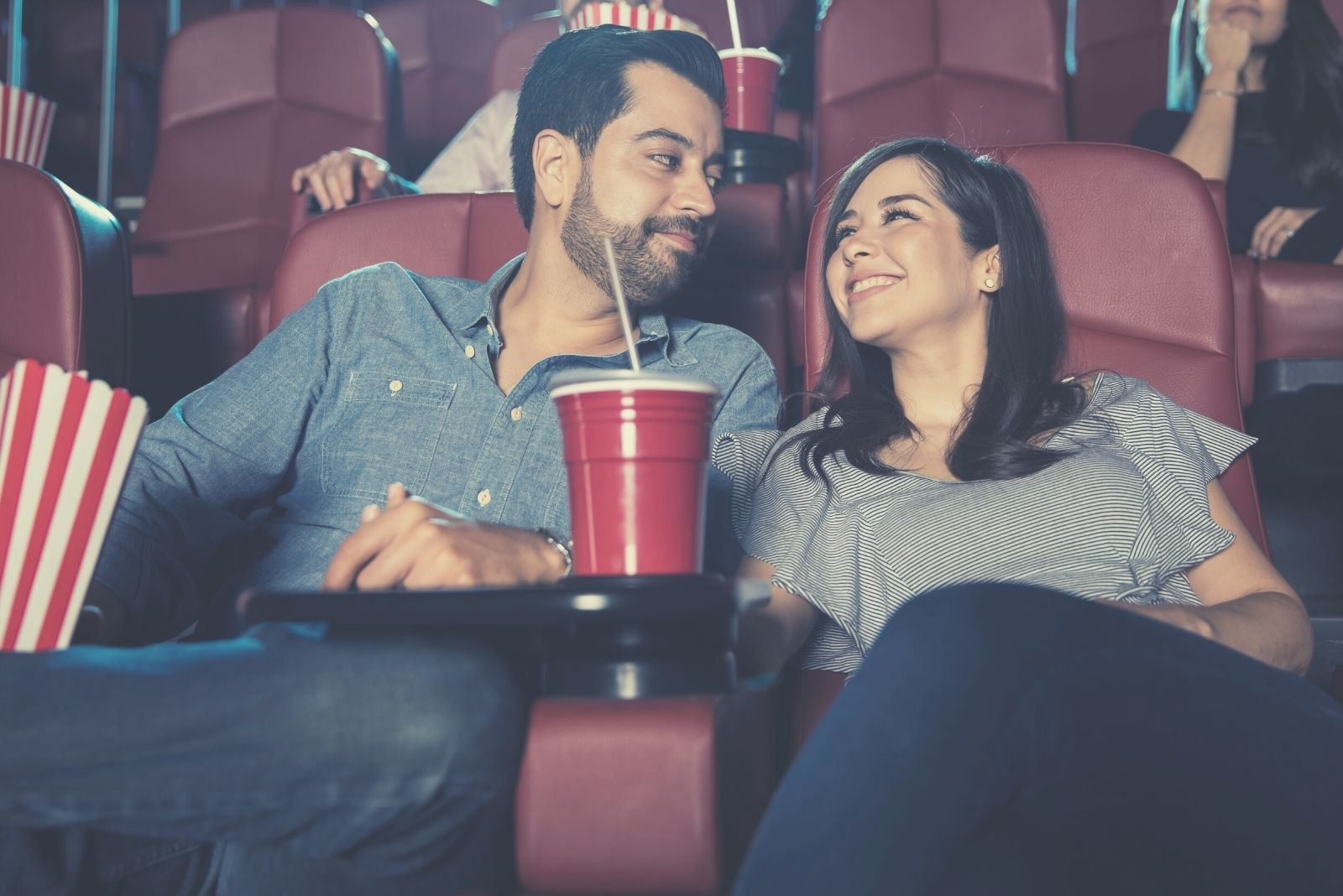married couple dating watching movies in the moviehouse smiling at each other