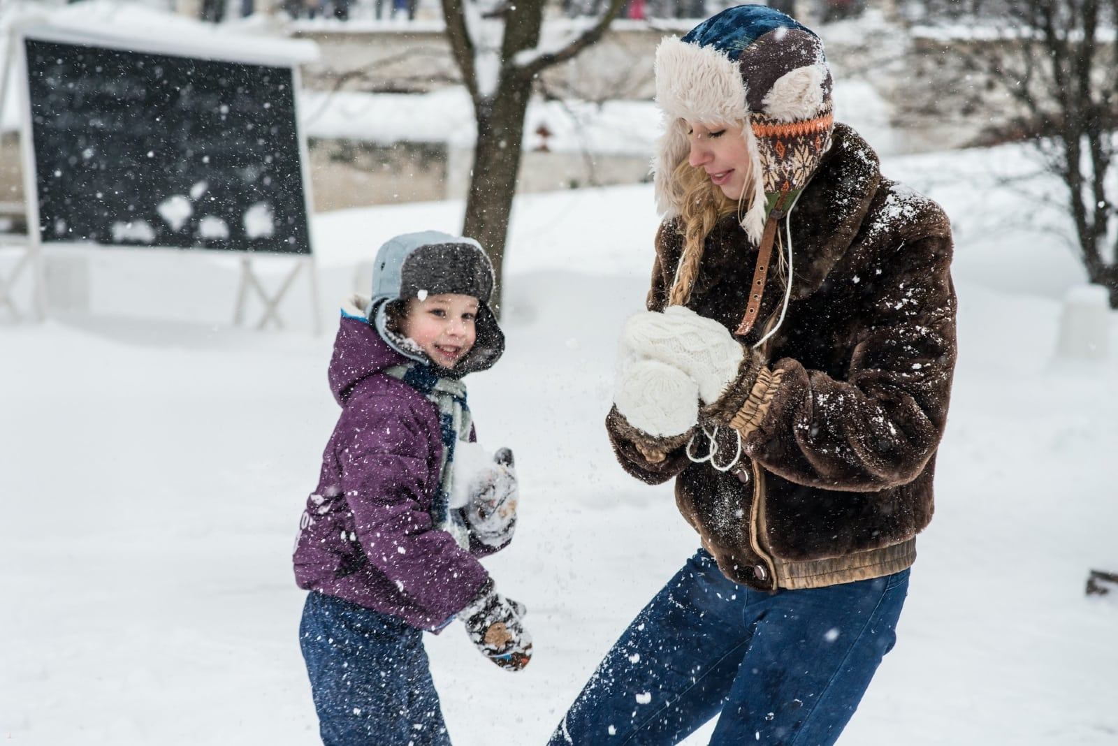 mother playing with son in snow