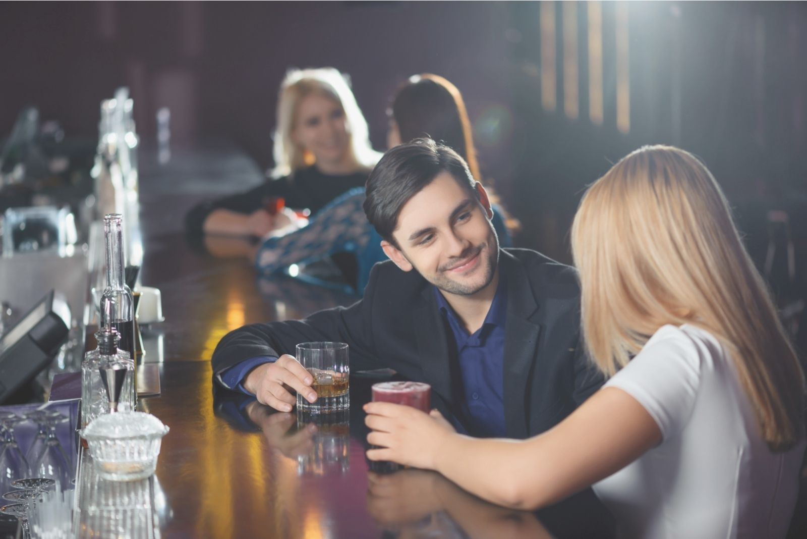 office female colleague drinking with her male colleague at the bar