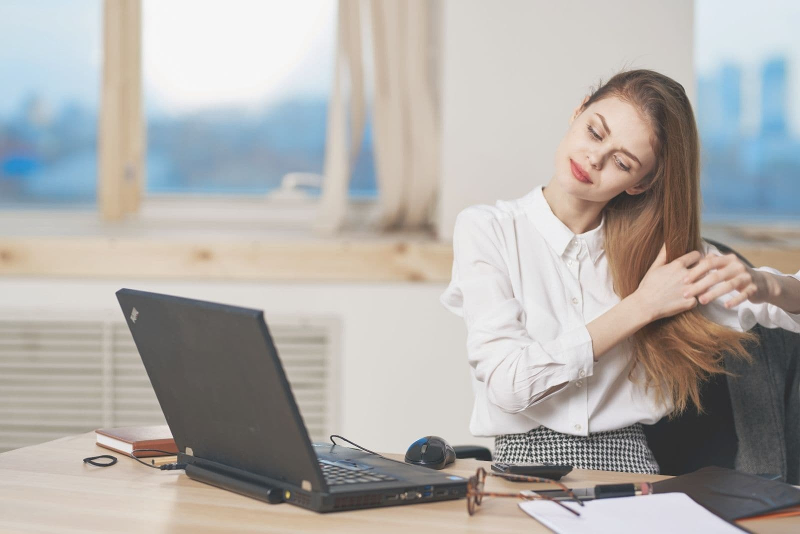 office female worker fixing her hair while working in the office