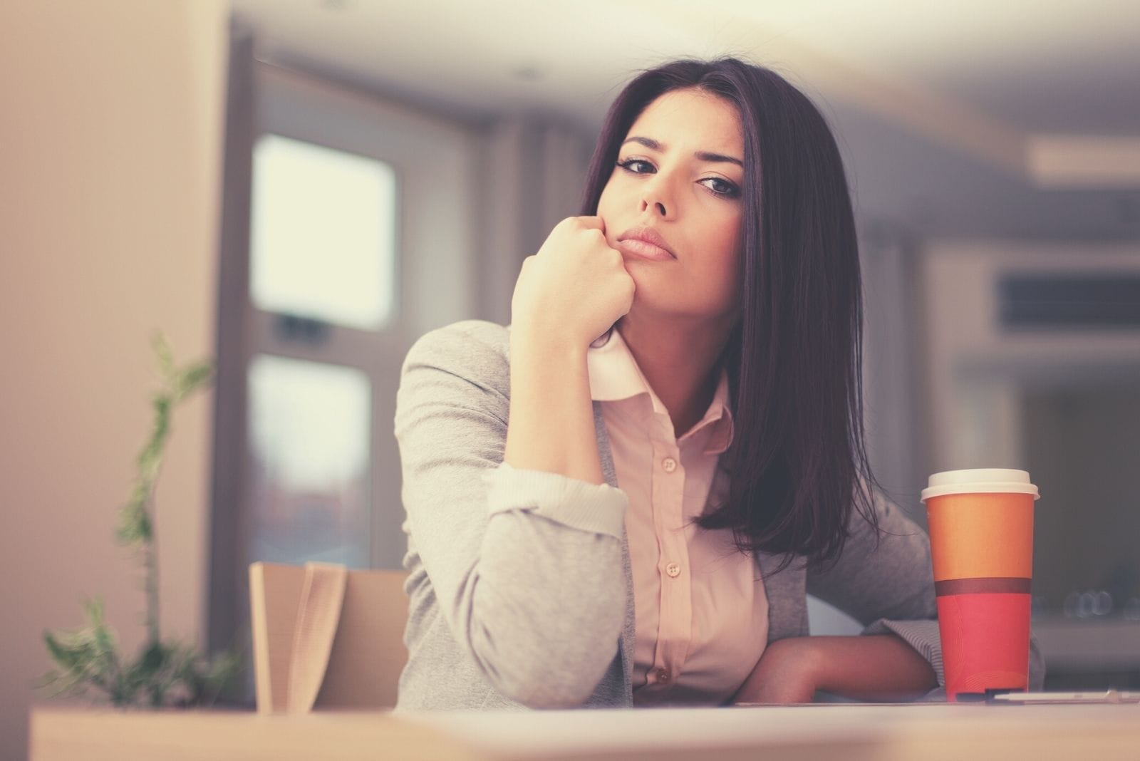 pensive businesswoman staring at the camera sitting by the office table