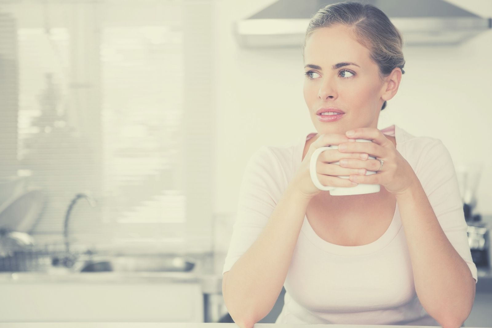 pensive house wife drinking coffee in the kitchen