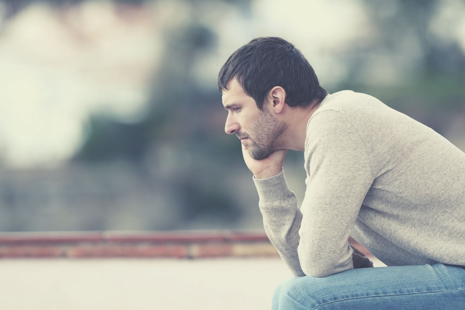 pensive worried man sitting outdoors with head leaning on his hand