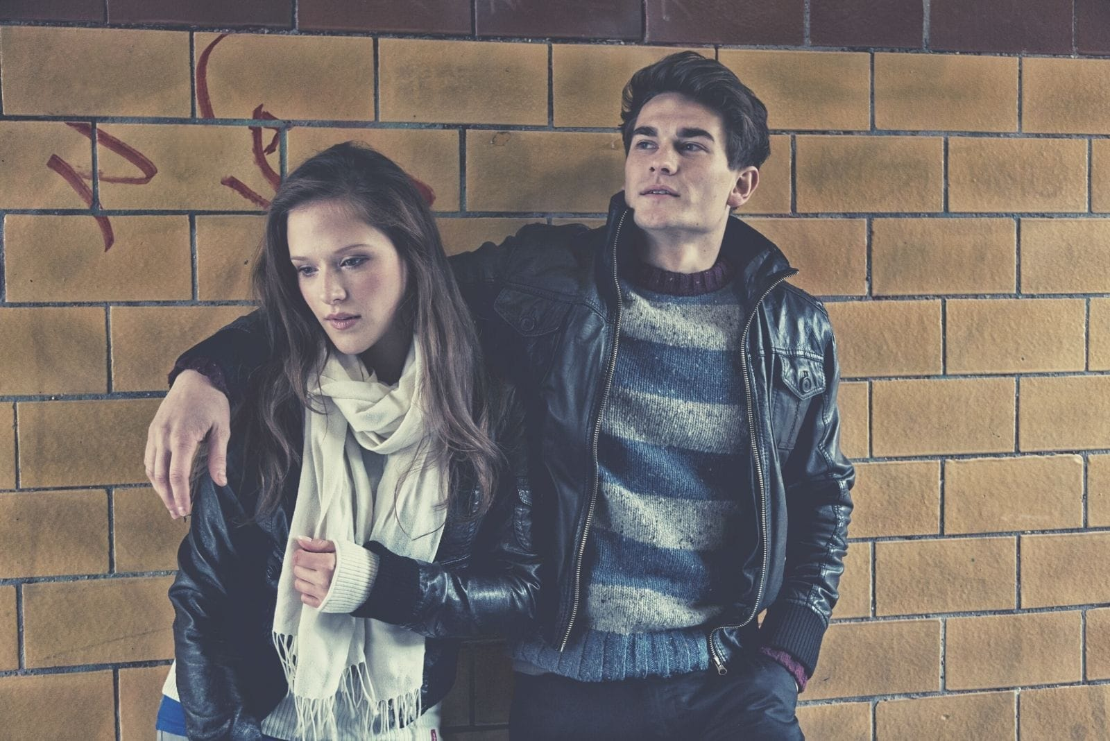 pensive young couple wearing leather jacket standing againg brick wall with hand of the man around the woman's shoulders