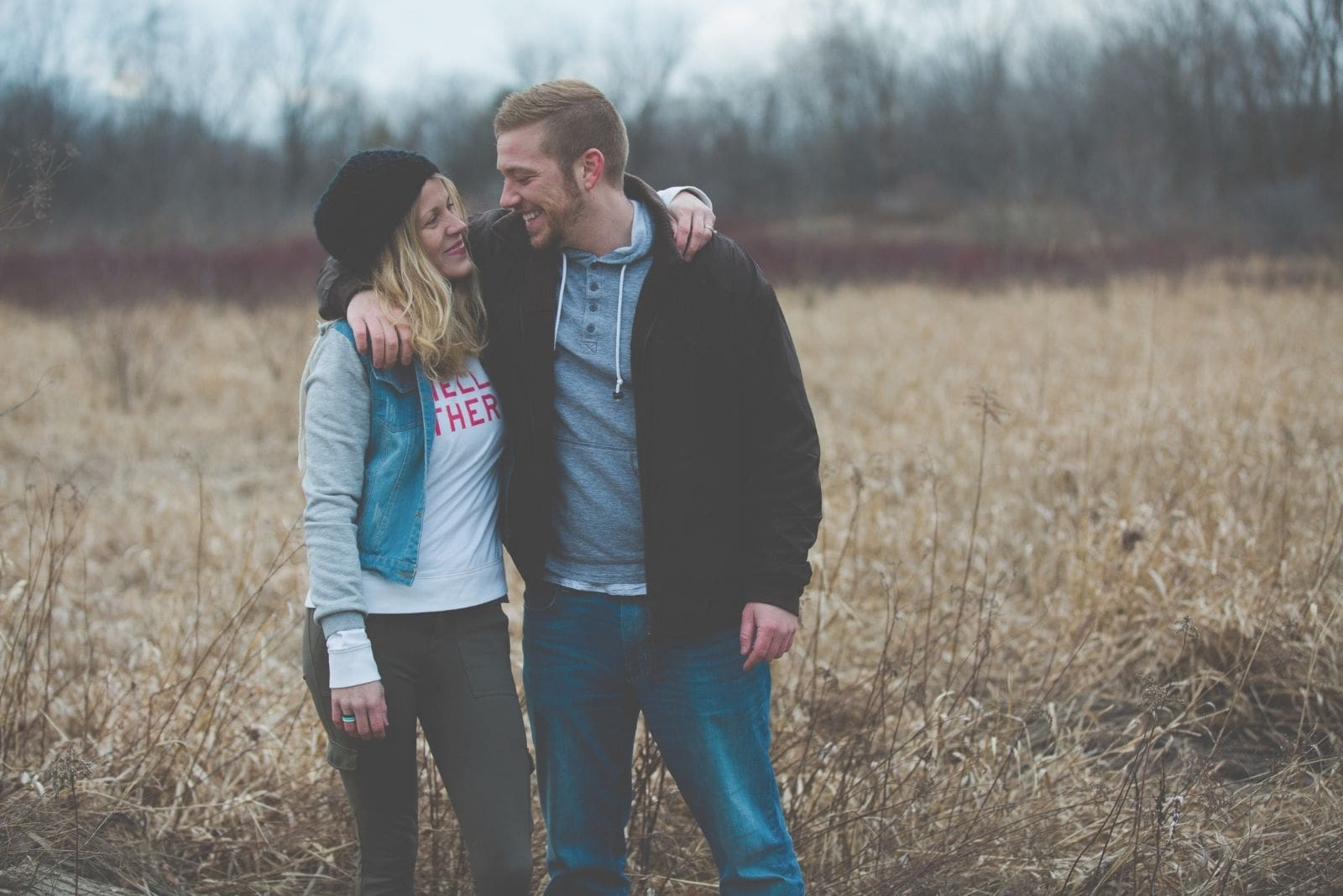 photo of a couple standing side by side in the field and looking at each other with hands wrapped around each other