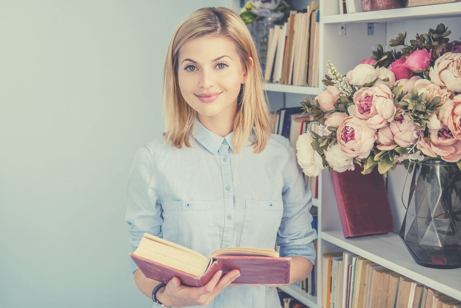 portrait of a positive woman holding a book and smiling and looking at the camera