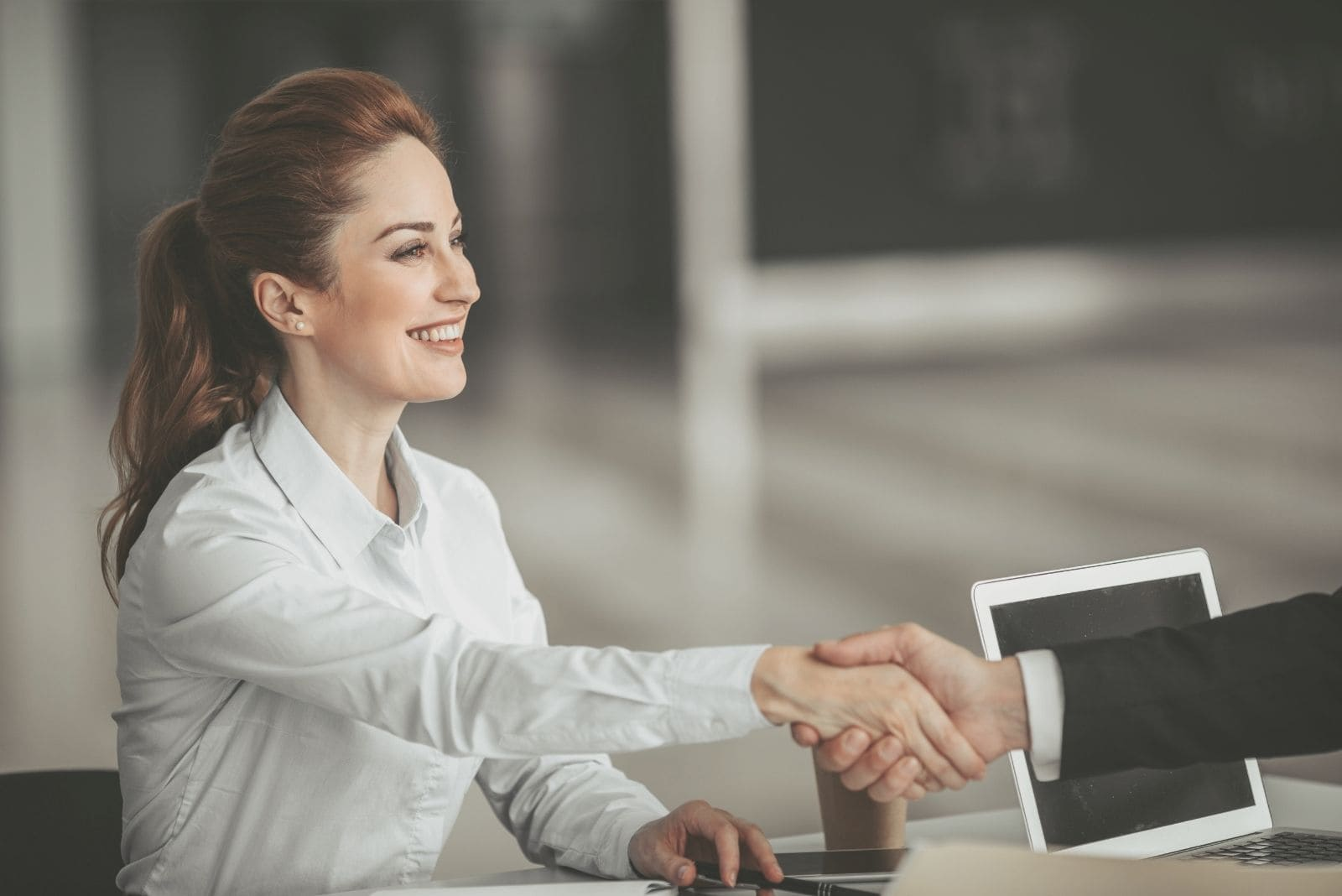 positive business woman handshaking a man's arm inside the office