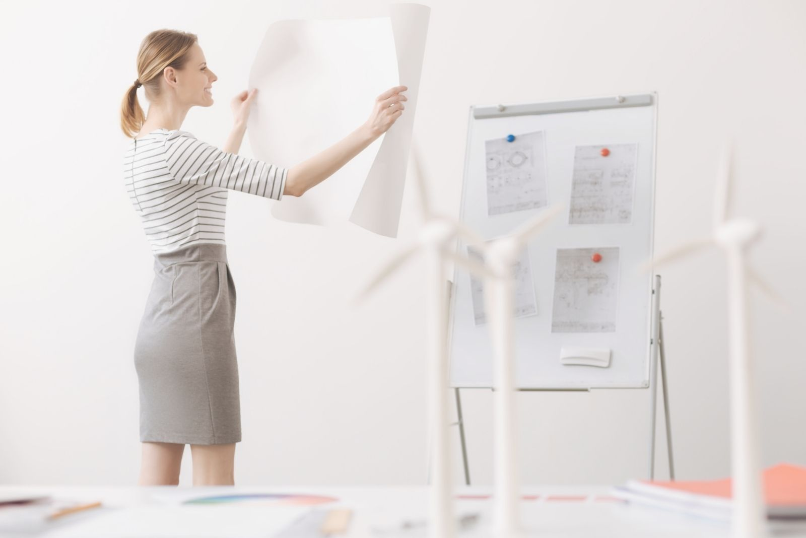 positive female engineer looking and holding a blueprint inside the office