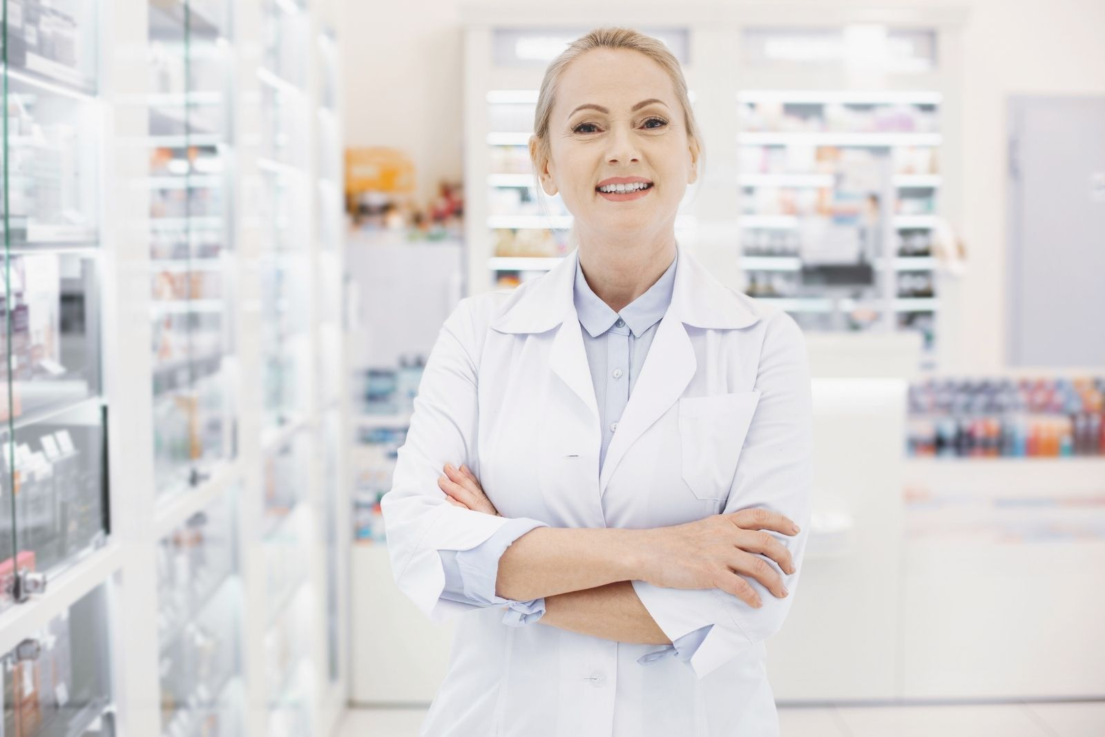 positive female pharmacist standing inside the pharmacy with arms crossed