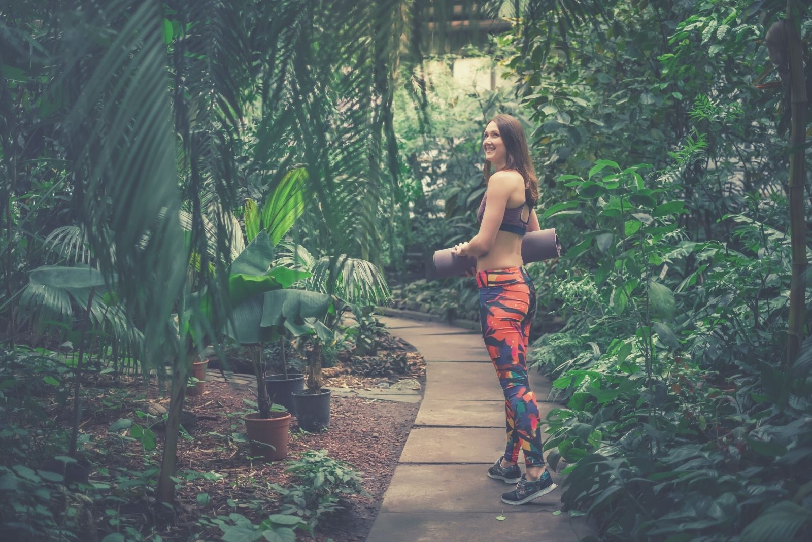 positive female yoga instructor posing at a greenhouse bringing a mat