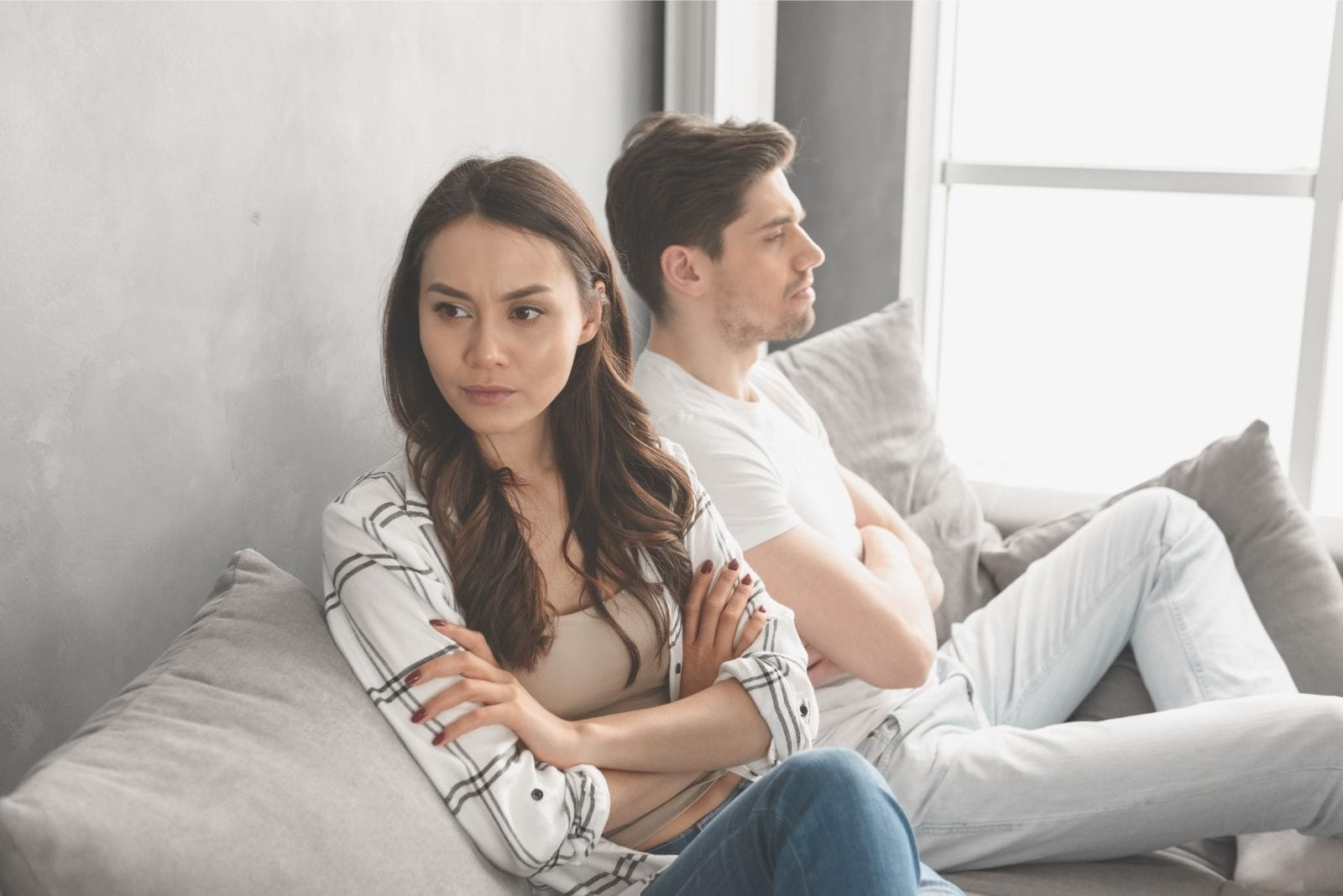 resentful woman sitting next to a guy after an argument