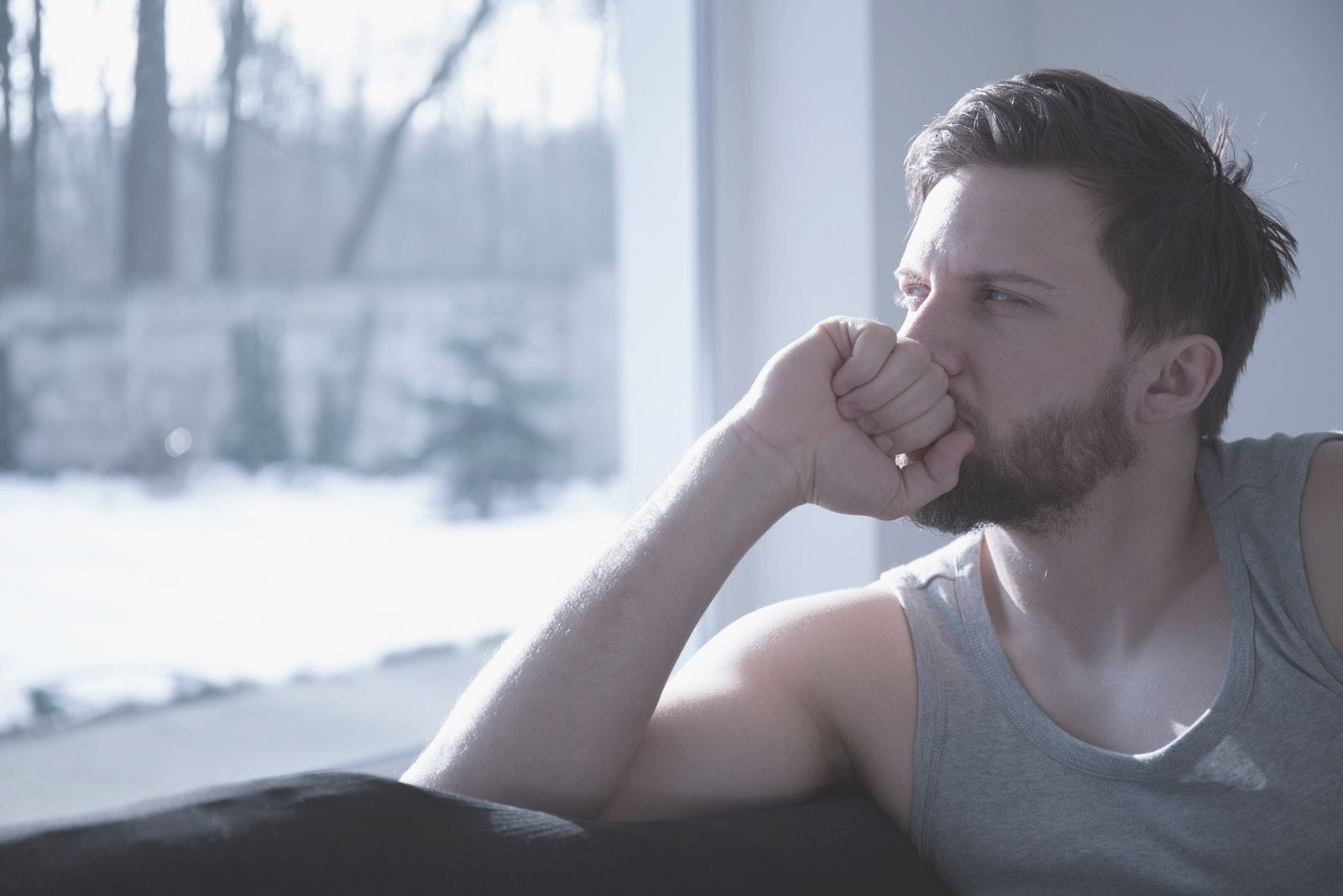 sad man deeply thinking sitting near the windows with hand on the mouth