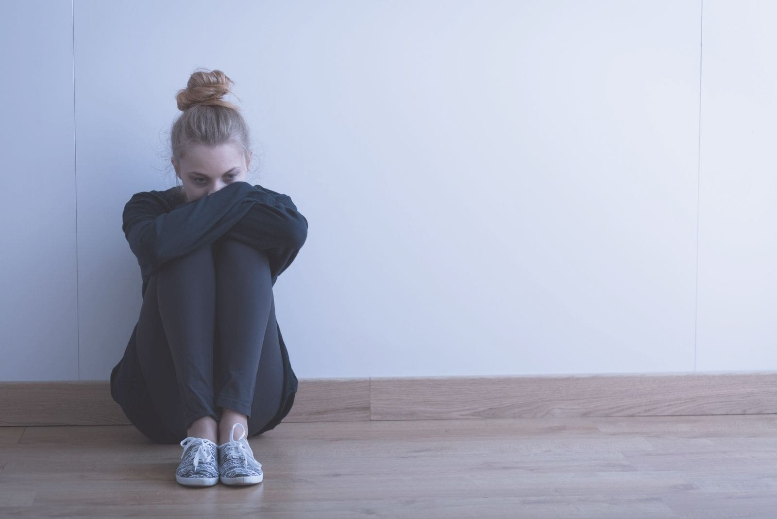 sad woman wearing black sweater and pants sitting on the floor inside an empty room