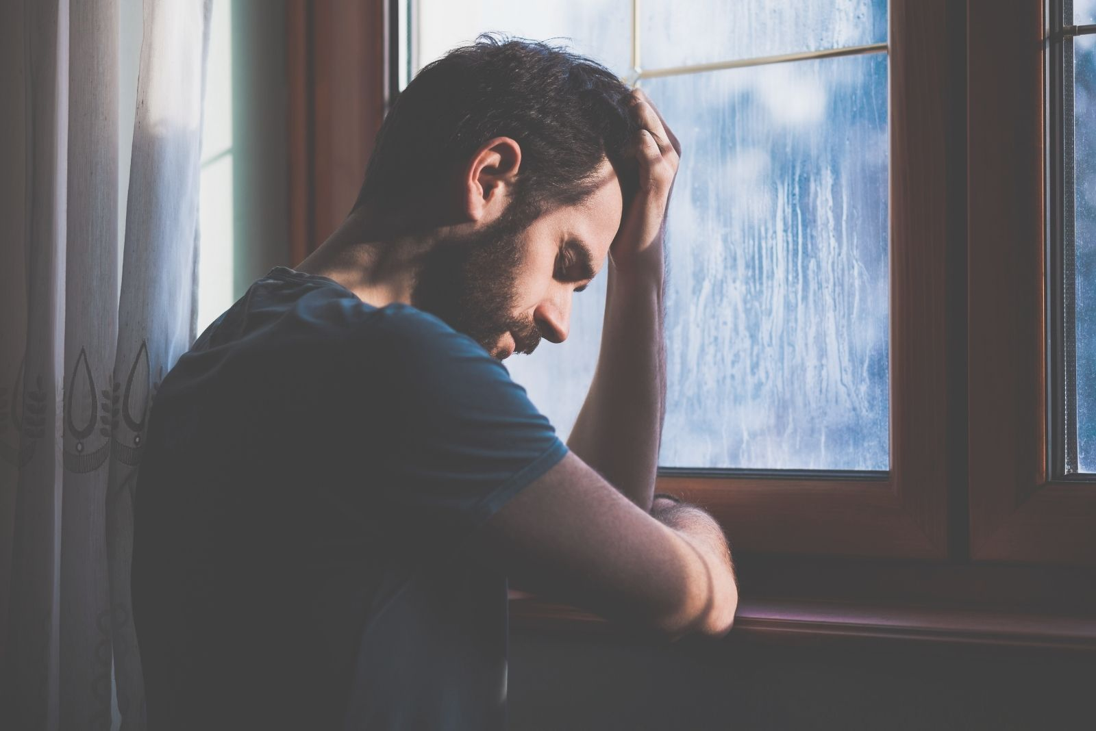 sad young man in regret in the window of a dark room