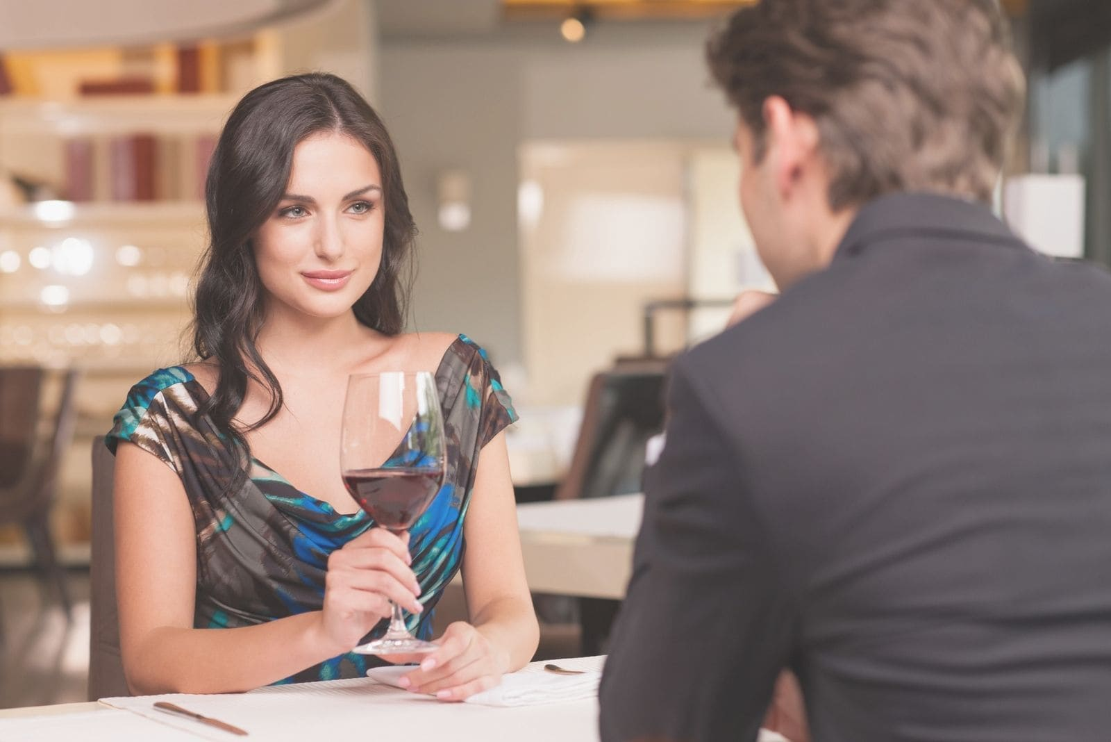 seducing beautiful woman looking at her boyfriend during a dinner date in a restaurant
