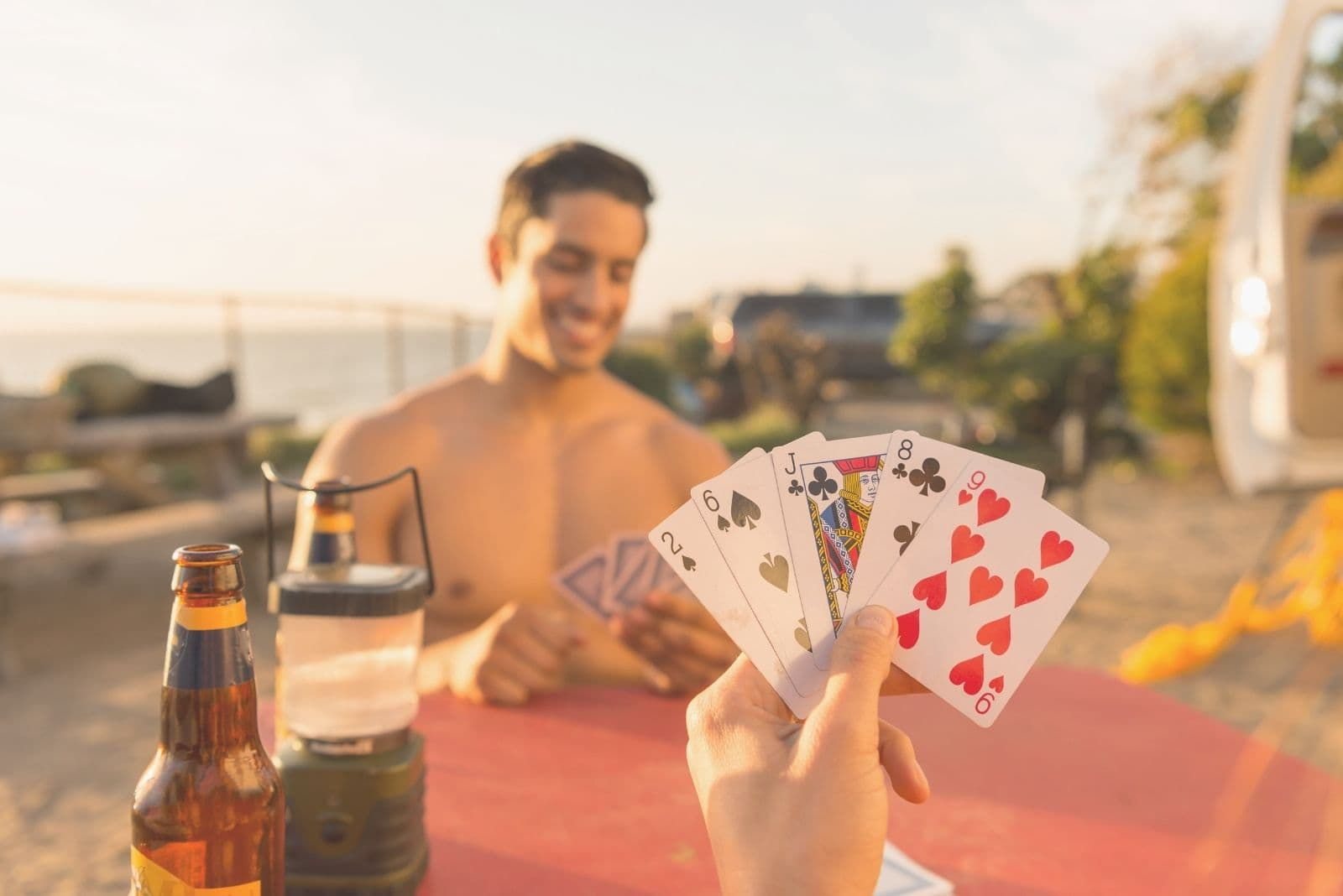 shirtless man playing cards outdoors with his girlfriend in cropped image