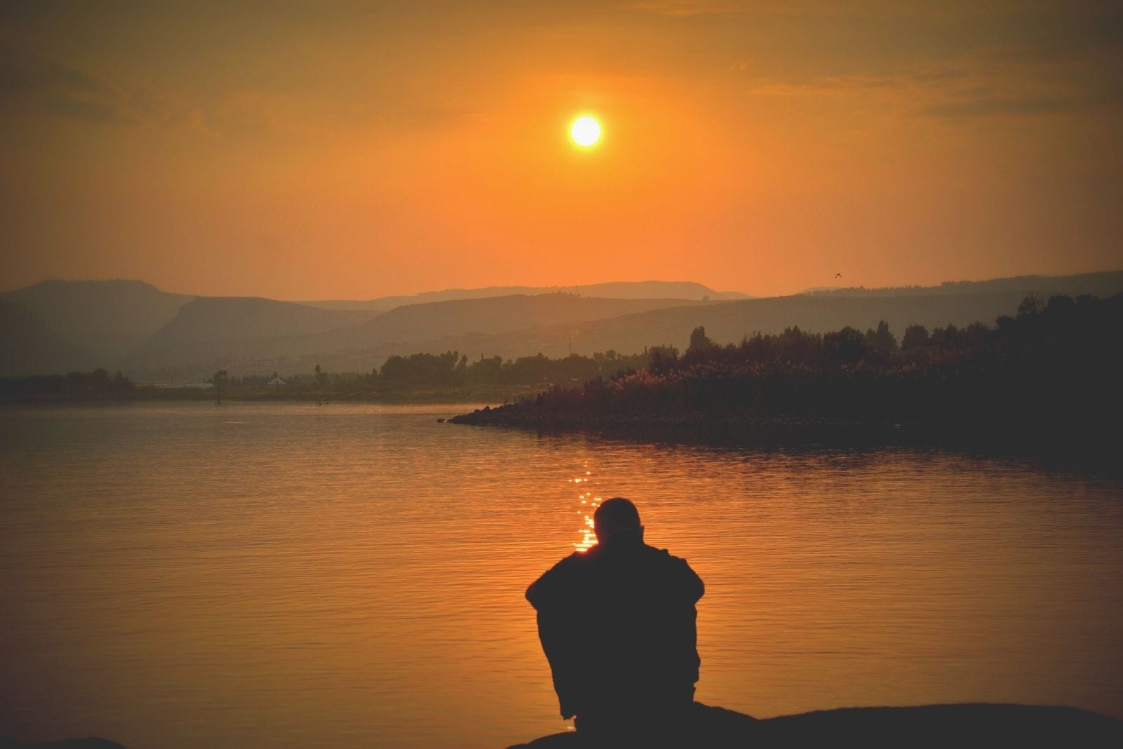 silhouette of a person sitting near the lake with the moon above