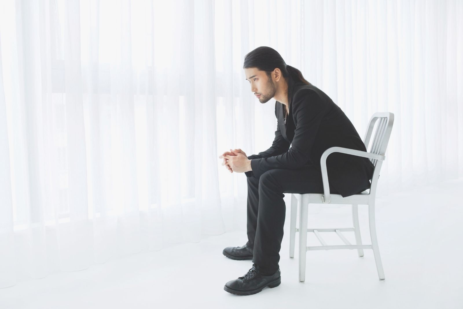 smart young japanese man sitting and thinking deeply